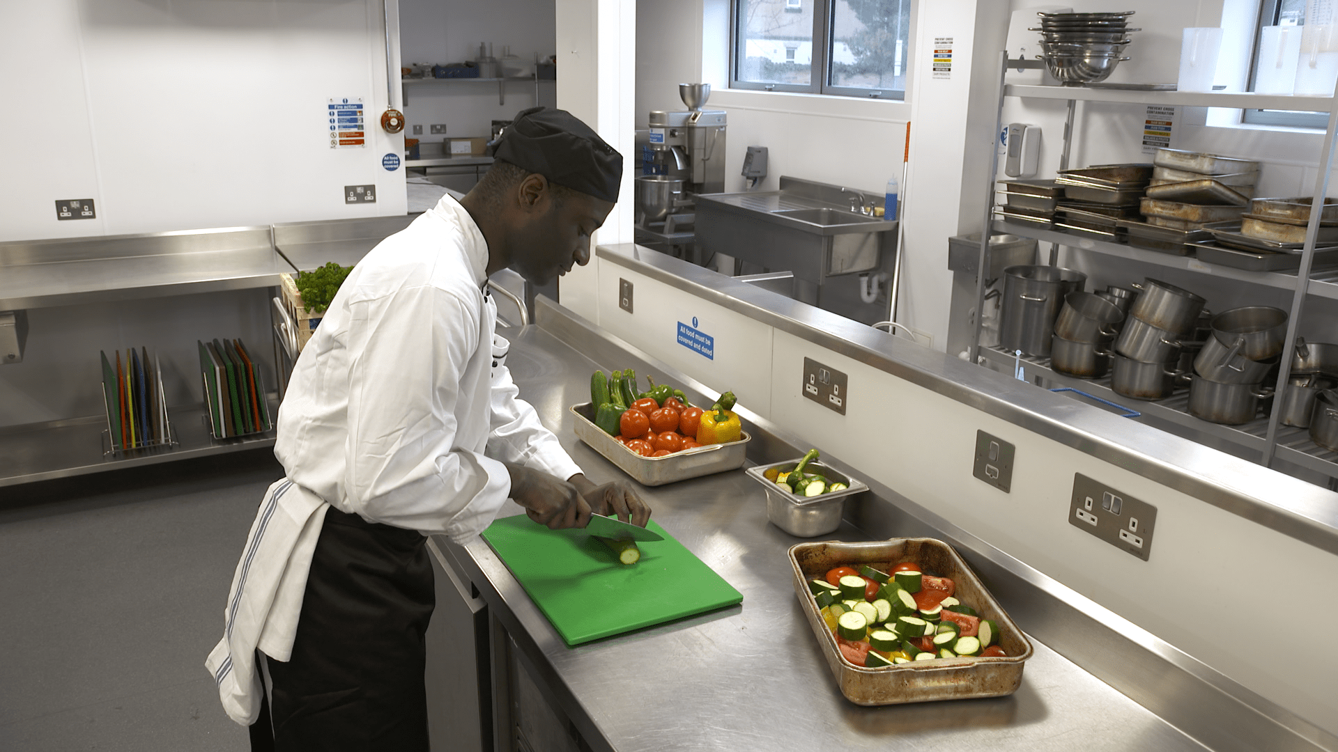 A chef in the kitchen preparing vegetables, taken from iHASCO's online food safety & hygiene course.