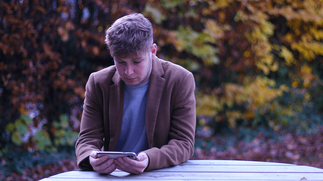 An employee sat outside at a table looking at a phone screen.