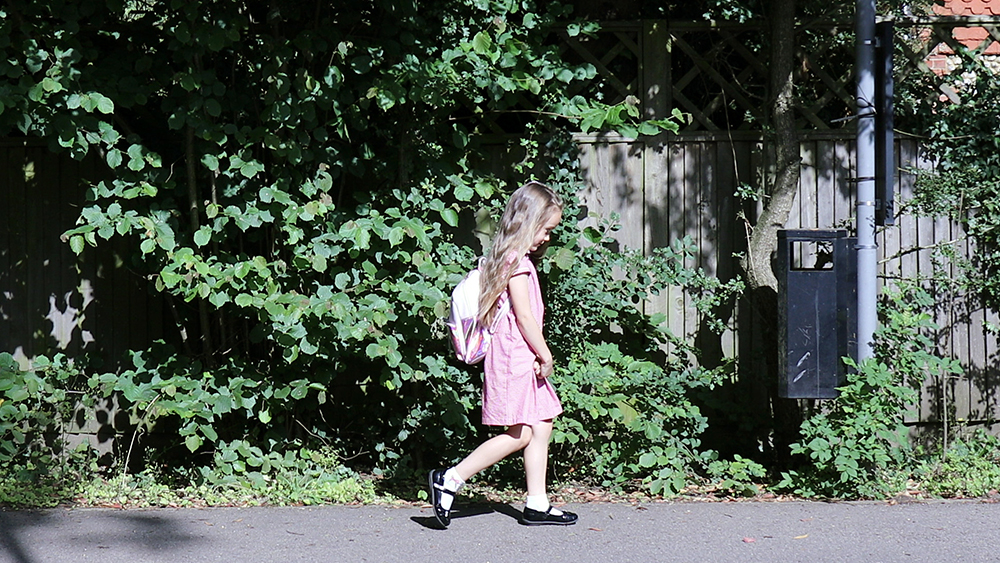 A young girl walking to school