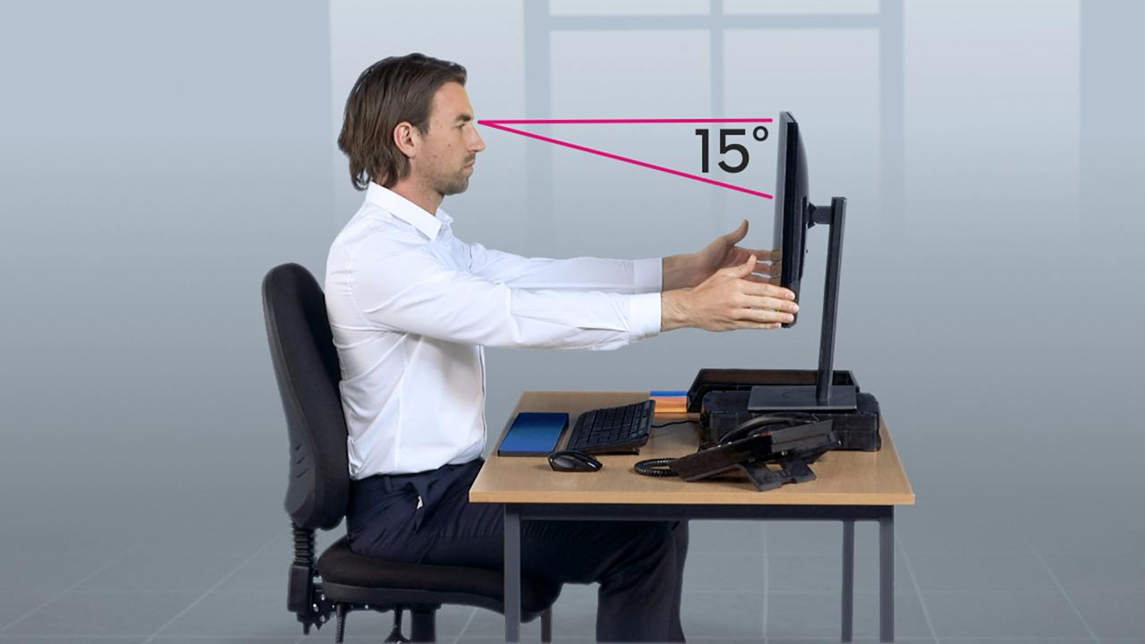 Man adjusting computer screen height - DSE training