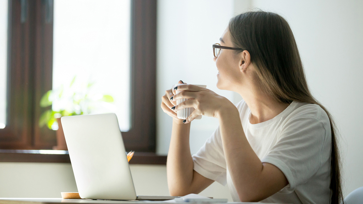 A woman with a coffee at her work desk