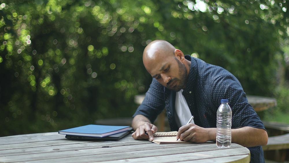 A man sat outside writing