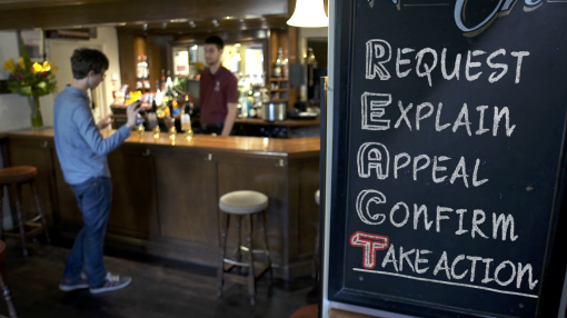 Image of a blackboard showing the REACT technique, something used by many staff working in licensed premises to calm people down.