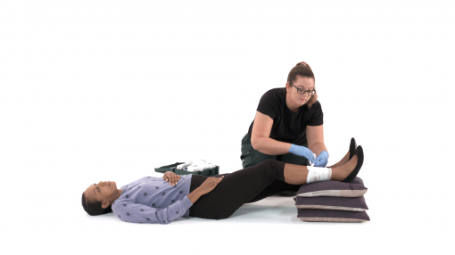 Paramedic helping a patient with an injured leg