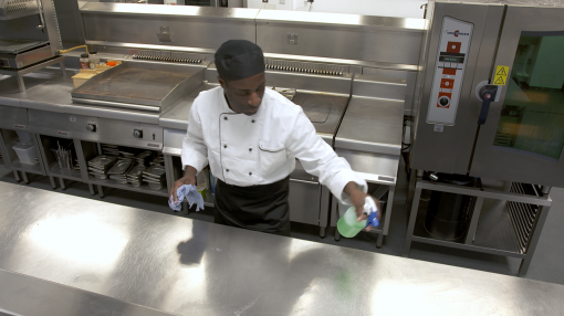 A chef cleaning down his workstation